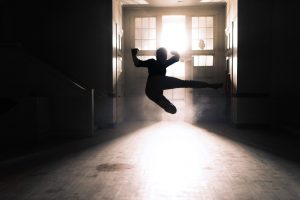 silhouette of a woman jumping in the air, doing a roundhouse kick