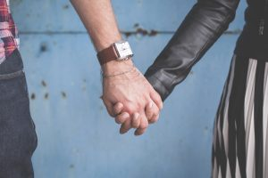 A close up of a couple holding hands
