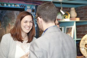 One woman smiling during a conversation with a man at an event