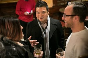 Young man speaks to a small group of other young professionals with beers in hand