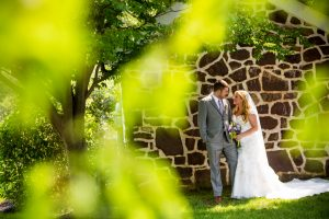 A young couple can be seen through the trees smiling and looking at each other on their wedding day