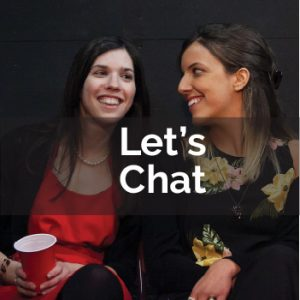 Two young women sitting next to each other and smiling