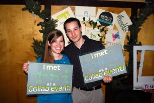 """Smiling couple with """"we met at the Collaborative"""" signs"""