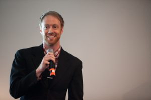 A young man in a suit smiles as he speaks into a microphone