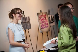 Smiling woman standing and chatting while tabling at Launch Night event