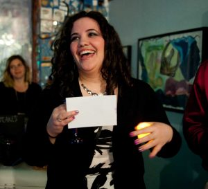 A young lady smiles as she sings Shabbat prayers while holding a Shabbat candle