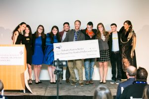 A group of 20s / 30s present a giant check to a Past Fellow on stage at Launch Night 2017