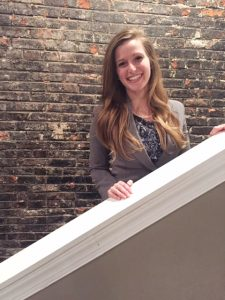 Emily stands on the stairs in front of a brick wall