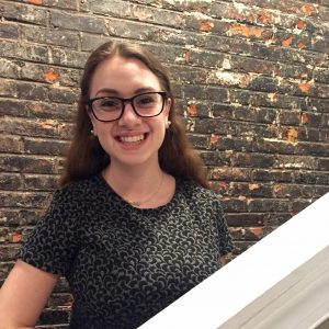 Allison, a young woman wearing glasses, smiling on the stairs in front of a brick wall