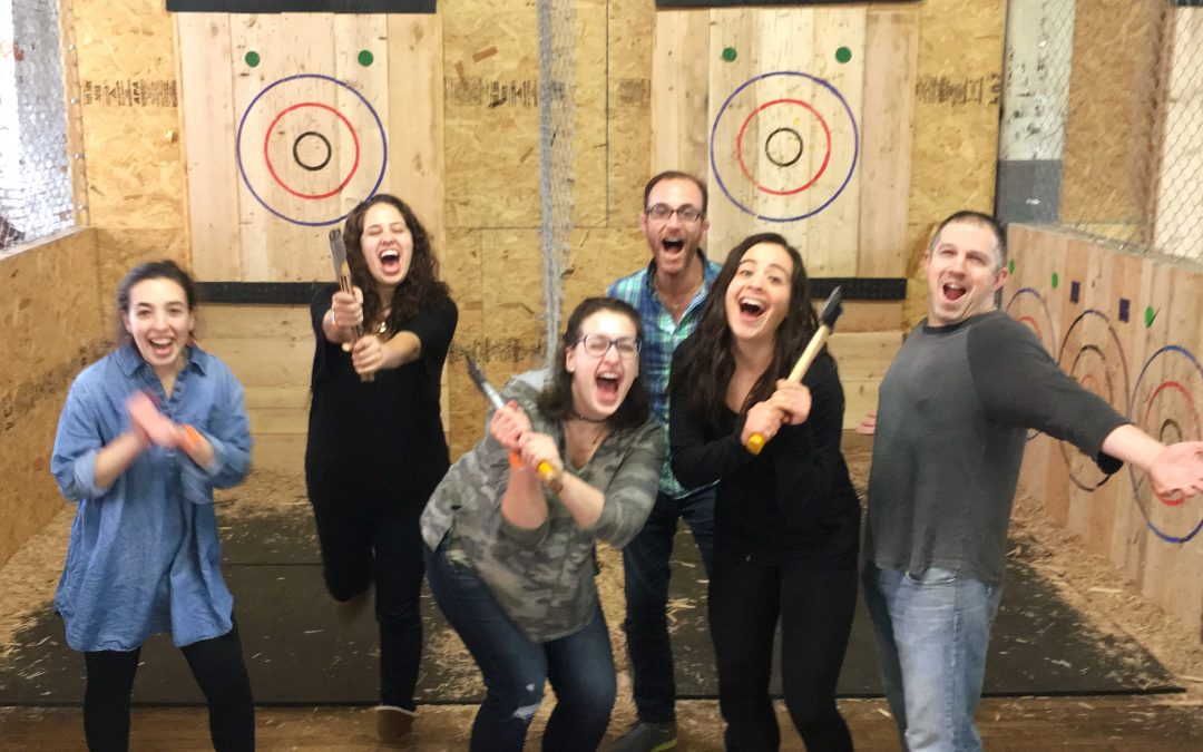 All five Tribe 12 staffers and our spring semester intern holding axes and shouting at the camera in front of the ax targets in the stadium