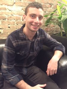 Zach smiles from the black couch in front of a brick wall