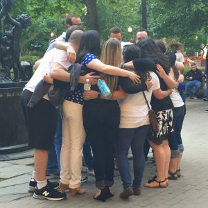 A group of young professionals gather together for a pre-performance huddle in a park on a summer day