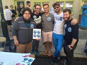 """A group of men wearing """"I heart Nice Jewish Boys"""" stickers pose and smile together on a warm fall day"""