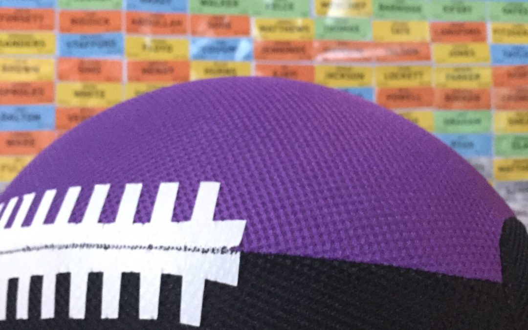Picture of a football with a fantasy football draft poster in the background