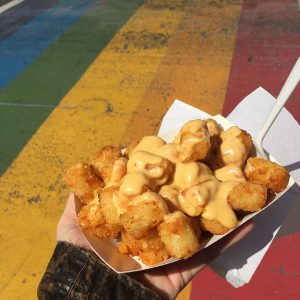 A carton full of cheesy tater tots held up in front of a rainbow sidewalk