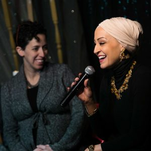 Two women sit beside each other on a panel, both women are smiling. One woman wearing a headscarf is speaking into a mic
