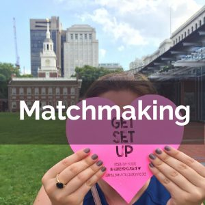 """Young woman with heart shaped paper in front of face that reads """"Get Set Up"""" in front of Independence Hall, Philadelphia"""