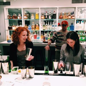 Two girls smile together as they shake cocktails behind a bar