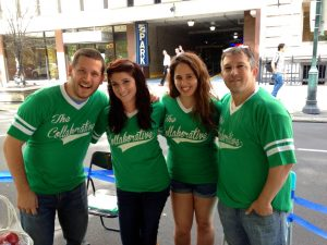 """Two men and two women all wear matching green vintage-style baseball shirts with the name """"The Collaborative"""""""
