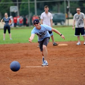 """Shot of a man """"pitching"""" a kickball toward home plate on a sunny day"""