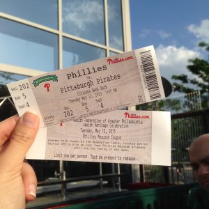 A hand holds a pair of Phillies v Pittsburgh tickets on a sunny day