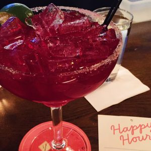 Large pink cocktail next to a Happy Hour menu
