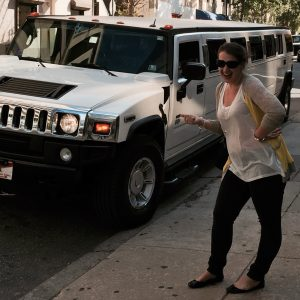 Rachel poses on the sidewalk next to a white stretch Hummer limo