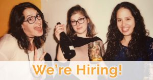 """Rachel Waxman, Rachel Abramowitz, and Danielle Selber pose together with a banner that says """"We're Hiring"""""""