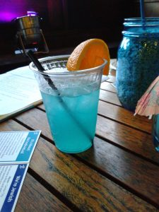 Blue cocktail with an orange slice garnish sits on a wooden cocktail table