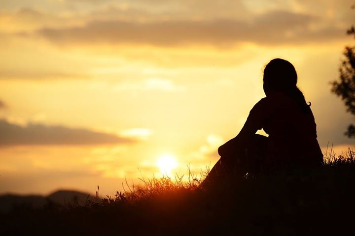 A silhouette of a woman sitting on a hill and watching the sunset