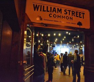 """A shot through an open door looking into a crowded room decorated with string lights. Sign over the door says """"William Street Common"""""""