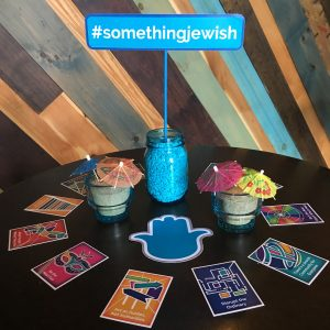 A cocktail table is decoarted with 12 colorful collectable cards, a teal hamsa, and sand-filled mason jars with cocktail umbrellas