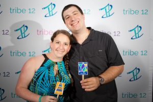 A young woman and a young man smile together and hold up cards while standing in front of a Tribe 12 step and repeat