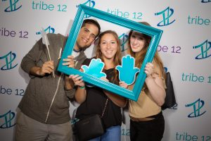 Three young professionals pose with teal props in front of a Tribe 12 step and repeat