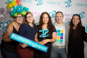Five staff members pose for a picture with Tribe 12 props and party decorations