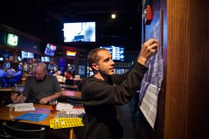 Dave adds a sticker to the football draft board at a sports bar