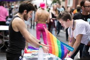 Two young men leaning over a table with a rainbow flag on it. One is chatting and the other is adding his email to a list.