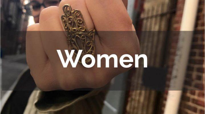 Woman wearing hamsa ring seems to be punching the camera
