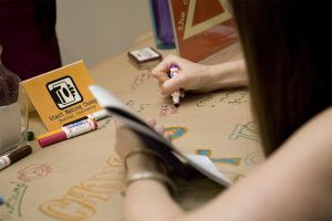 A woman writes an idea on a large piece of butcher paper