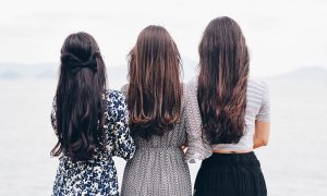Three women with long brown hair stand shoulder to shoulder overlooking the ocean