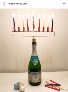 A copper menorah is attached to a corn that can be stuck in your wine bottle