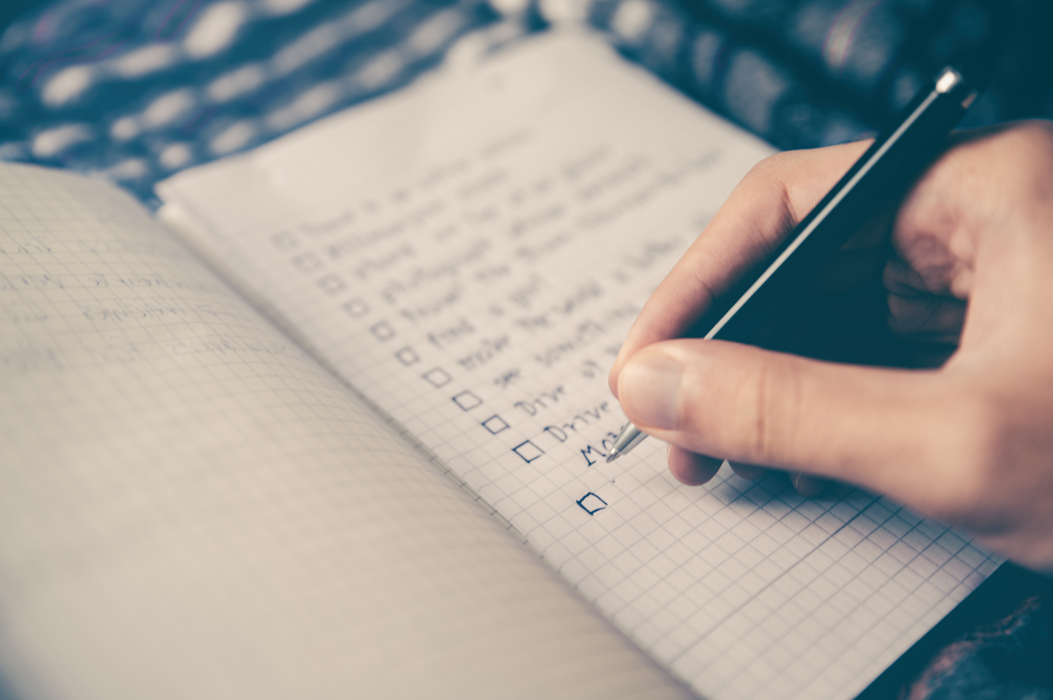 Person writing a checklist with a pen in a notebook