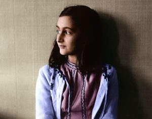 An actress dressed as Anne Frank looks out a window and off in the distance