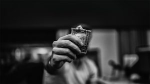 Black and white image of someone holding $1 bill up to the camera