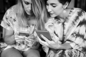 Two girls looking together at each other's phones