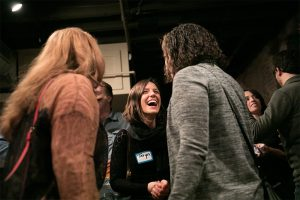 Taryn laughs mid-conversation while networking with two other Fellows