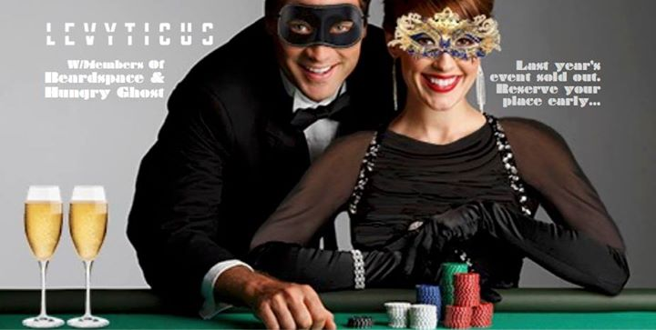 A man and a women in cocktail attire lean over a Poker table in masquerade masks