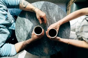 two people drinking coffee, shot from above