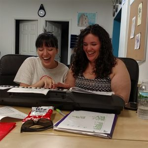 Two young women laugh as they play a keyboard together, surrounded by papers and clipboards full of sheet music