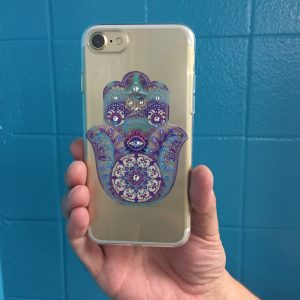 Someone holds a hamsa phone case up in front of a teal wall